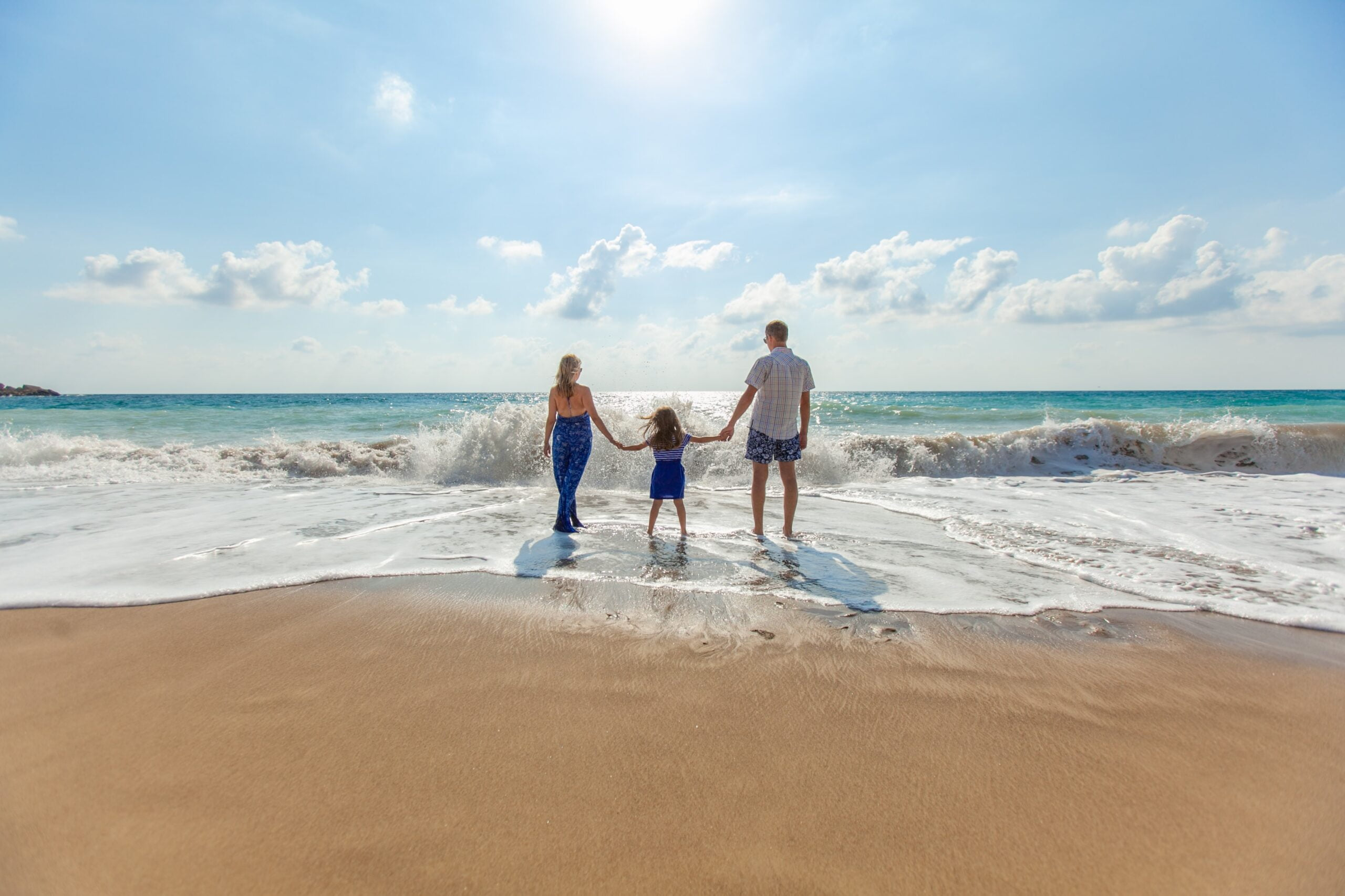 A family holiday hands on the shoreline of a sunny beach
