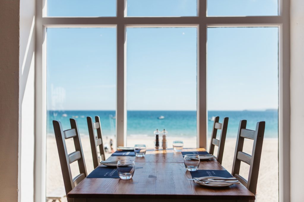 4 seater table situated directly in front of large window looking over the beach and sea.