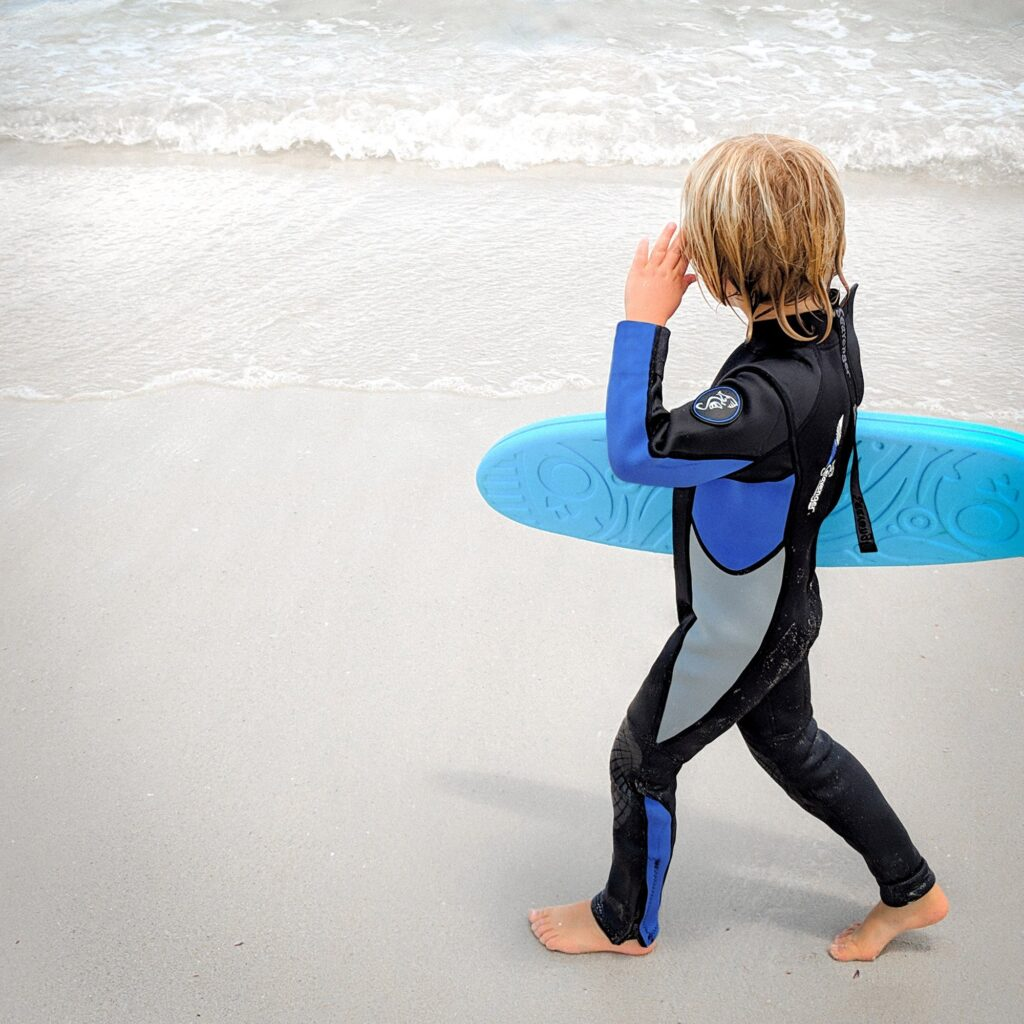 Young child wearing a wetsuit and holding a surfboard on a rainy day in Cornwall