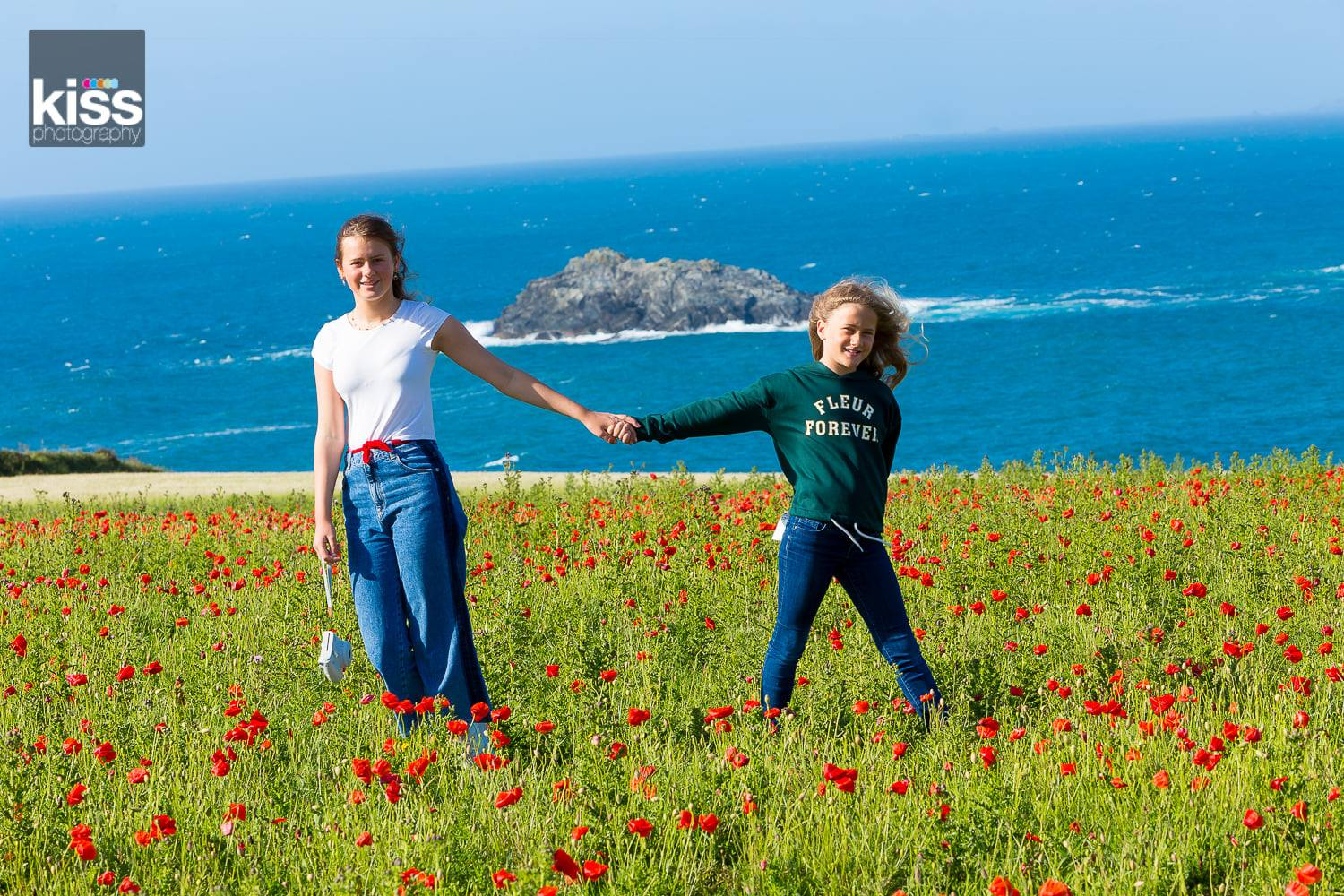 Sisters holding hands in poppy field overlooking the sea as part of a family photo shoot in st ives