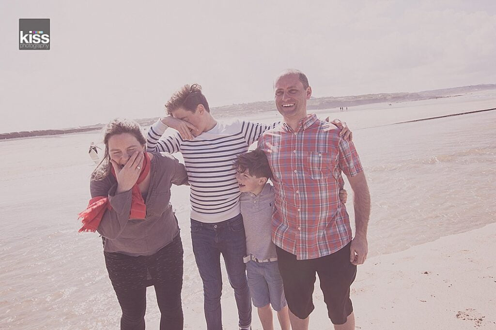 Family of four on the beach giggling during a family photoshoot in st ives