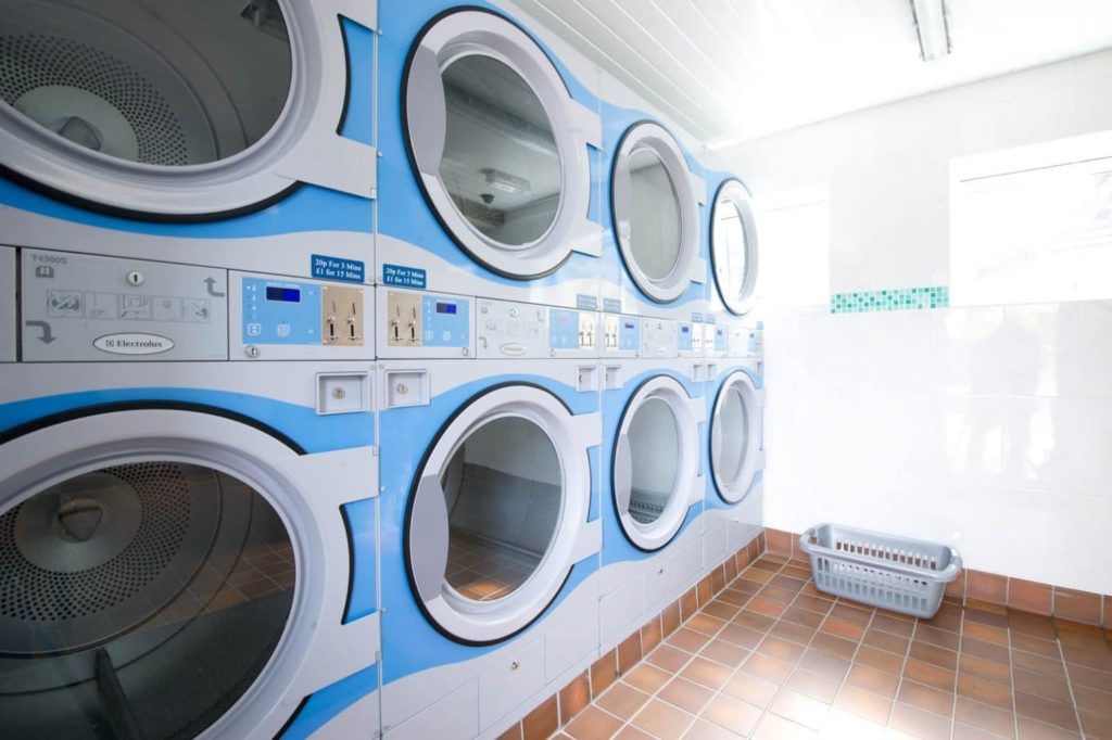 Side view of 6 coin operated tumble dryers in Polmanters laundry room