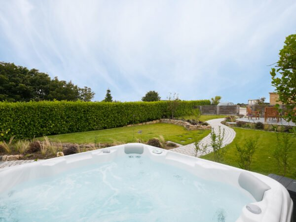 Hot tub in the landscaped garden of Polmanter Touring Park