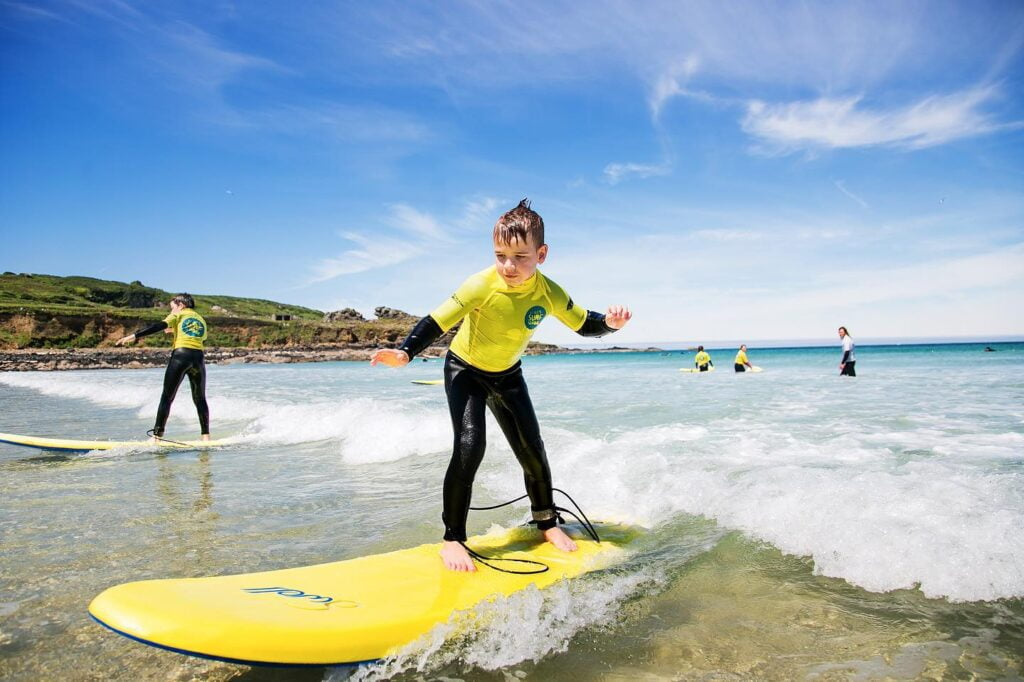 Young boy standing on a surfboard in the sea learning to surf with St Ives Surf School in West Cornwall