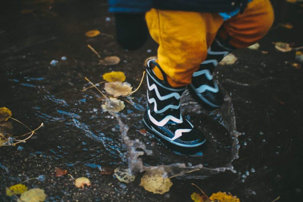 Child splashing in the puddles on a rainy day in Cornwall