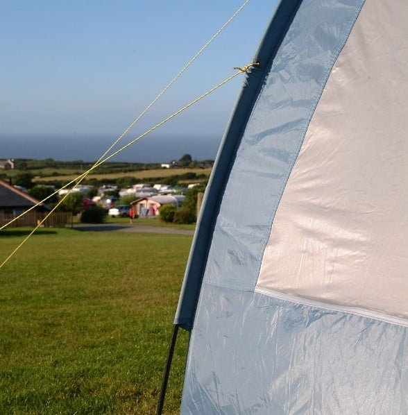 Blue tent pitches in the Movah field with views of the sea