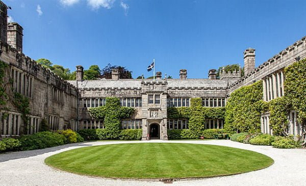 Lanhydrock house and lawn with a bright blue sky