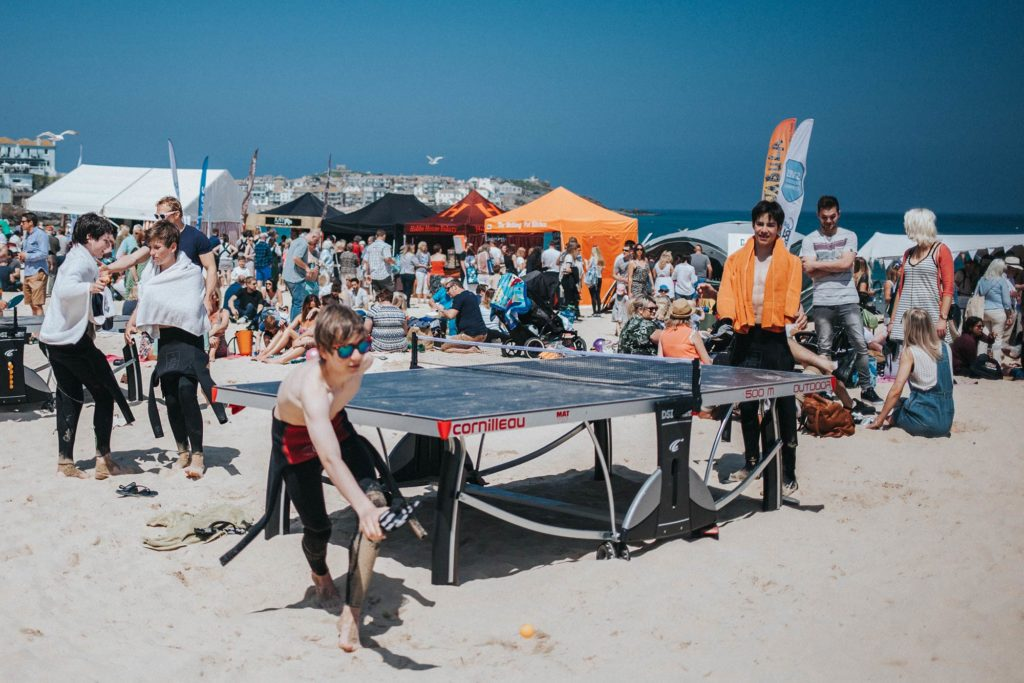 Children play table tennis on a busy beach with food stalls in the background